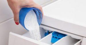 Woman pouring washing powder into the washing machine